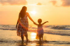 A mother and daughter in pretty dresses walking along an ocean beach at sunset
