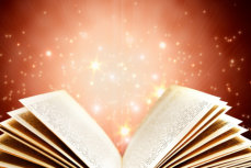 An open book with sparkles of light coming from the pages
