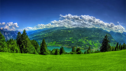 Green meadow overlooking mountains with clouds in the background