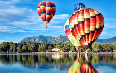 Hot air balloons flying over a lake